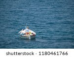 Fisherman in traditional wooden boat at sea, facing awaz from viewer, going out to sea, daylight, authentic and unstaged, mediterranean style, could be Italy, Greece, Croatia or Adriatic sea - stock photo