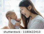 mother and baby playing in...   Shutterstock . vector #1180622413