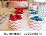 raspberries and blueberries in... | Shutterstock . vector #1180648840
