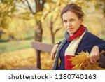 young beautiful woman in autumn ... | Shutterstock . vector #1180740163