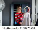 young girl choose a dress at... | Shutterstock . vector #1180778563