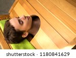 young woman in cedar barrel.... | Shutterstock . vector #1180841629