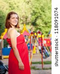 Portrait of pregnancy woman against  playground area - stock photo