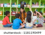 Small photo of Asian female teacher teaching and asking mixed race kids hand up to answer in classroom,Kindergarten pre school concept