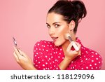 Stock photo beautiful young brunette woman applying blusher to her cheek using a cosmetic brush and small 118129096