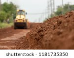 Small photo of Yellow vibratory soil compactor working on highway construction site, Yellow vibratory soil compactor