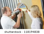 Assistant seller help choosing paint color and demonstrating matching samples to buyer at hardware store - stock photo