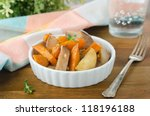 pears and sweet potatoes roasted with mustard in a white bowl on - stock photo