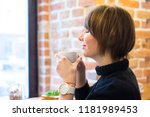young woman drinking coffee in... | Shutterstock . vector #1181989453