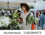 beautiful woman buying kale at... | Shutterstock . vector #1182084073