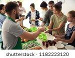 volunteers serving food for... | Shutterstock . vector #1182223120