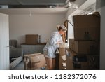 mature woman is unpacking boxes ... | Shutterstock . vector #1182372076