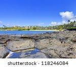 Island Maui lava beach with resort buildings on the back. - stock photo