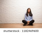 young indian woman sit against... | Shutterstock . vector #1182469600