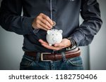 business hand putting coin into ...   Shutterstock . vector #1182750406