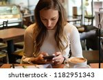 woman working on her phone at... | Shutterstock . vector #1182951343