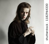 Small photo of Gothic halloween clothes. Mystical conspiracy. Punk with long hair. Cunning vampire with hairdo. Spooky outfit for halloween party. Mystical vampire in gothic punk shirt devises conspiracy.