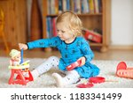 Small photo of Adorable cute little toddler girl playing with doll. Happy healthy baby child having fun with role game, playing mother at home or nursery. Active daughter with toy.