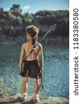 Small photo of Caveman, manly man with stone axe and bow hunting near river. Prehistoric tribal boy outdoors on nature. Young shaggy and dirty savage, warrior and hunter. Primitive ice age man in animal skin