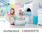 Small photo of Children in laundry room with washing machine or tumble dryer. Kids help with family chores. Modern household devices and washing detergent in white sunny home. Clean washed clothes on drying rack.
