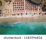 Aerial view of beautiful beach with orange sunbeds located in Saranda, Albania