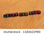 Small photo of The words of the happy new year are composed in colored letters of black cubes and lie on the sand.
