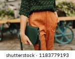 Blogging and street style concept. Autumn and winter outfit details. Young woman wearing casual orange trousers with green blouse and holding a green leather bag. Outdoors, selective focus.