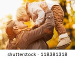 young mother rising baby up | Shutterstock . vector #118381318