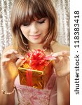 Young woman opens a box with a gift - stock photo