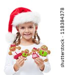 Happy little girl with santa hat holding gingerbread people family - stock photo