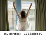 woman opening curtains in the... | Shutterstock . vector #1183885660