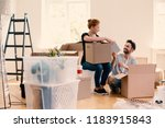 happy man and woman unpacking... | Shutterstock . vector #1183915843