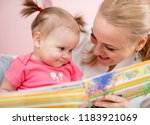 happy mom reading book to baby... | Shutterstock . vector #1183921069
