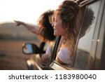 friends leaning out of a car... | Shutterstock . vector #1183980040