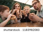 happy family eating burgers... | Shutterstock . vector #1183982083