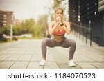 women exercise squats at city... | Shutterstock . vector #1184070523