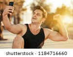cheerful sporty man showing... | Shutterstock . vector #1184716660