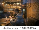 serious bar customer sit in... | Shutterstock . vector #1184731276