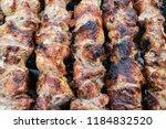 frying pork on a skewer over a...   Shutterstock . vector #1184832520