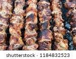 frying pork on a skewer over a...   Shutterstock . vector #1184832523