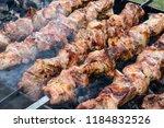 frying pork on a skewer over a...   Shutterstock . vector #1184832526