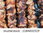 frying pork on a skewer over a...   Shutterstock . vector #1184832529