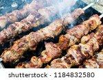 frying pork on a skewer over a...   Shutterstock . vector #1184832580