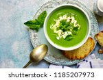 Small photo of Healthy broccoli soup in a bowl over light blue slate, stone or concrete background.Top view with copy space.
