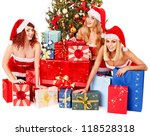 Women in Santa hat holding present near  Christmas tree. - stock photo