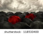 Standing out from the crowd concept, red umbrella among the blacks. - stock photo