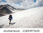 a mountaineer with a backpack... | Shutterstock . vector #1185497620