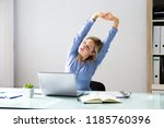 young businesswoman stretching... | Shutterstock . vector #1185760396
