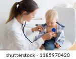 pediatrician examining baby boy.... | Shutterstock . vector #1185970420