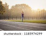 woman athlete on a morning run... | Shutterstock . vector #1185974299